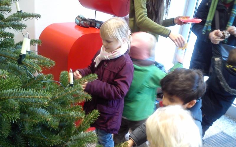 Kindergartenkinder schmücken den Weihnachtsbaum in der Sparkasse