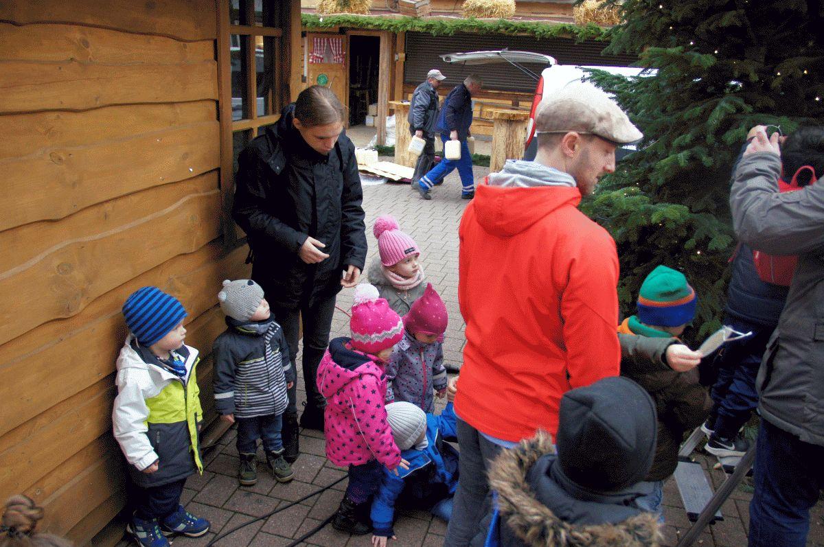 Kinder schmücken die Weihnachtsbäume auf dem Weihnachtsmarkt